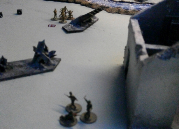 A German team attempts to make a sneaky advance from cover, but takes a volley of fire from the British team behind the tank trap.