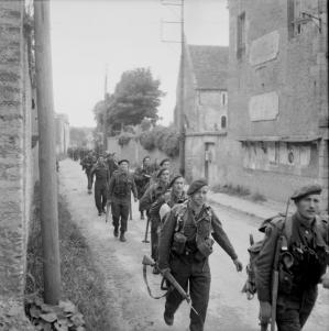 Royal_Marine_Commandos_attached_to_3rd_Division_for_the_assault_on_Sword_Beach_move_through_Colleville-sur-Orne_on_their_way_to_relieve_forces_at_Pegasus_B